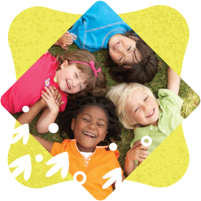 Closeup of four smiling children lying on their backs with heads touching and holding hands